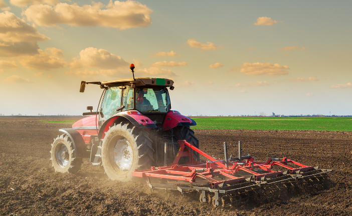 Farmer in tractor cultivating soil